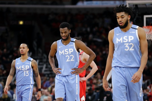 Timberwolves forward Andrew Wiggins reacts as he walks with guard Shabazz Napier, left, and center Karl-Anthony Towns after missing a basket during th