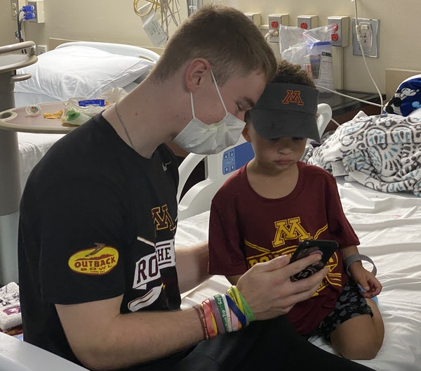 """Once Casey O'Brien was lured to Elias McNeal's room by a """"Go Gophers"""" shout, he spent some time with the toddler."""