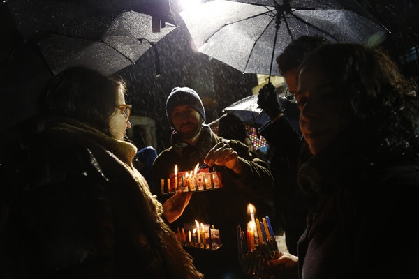 Alex Mizrahi, center, lights a candle on a menorah at a lighting for the last night of Hanukkah in Grand Army Plaza in the Brooklyn borough of New Yor