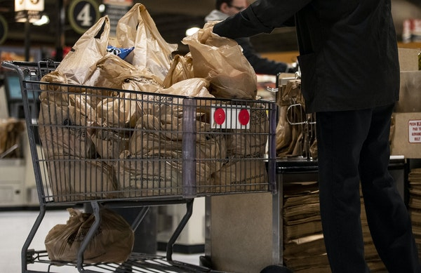 A shopper loads up a cart full of plastic bags at a grocery store in November.