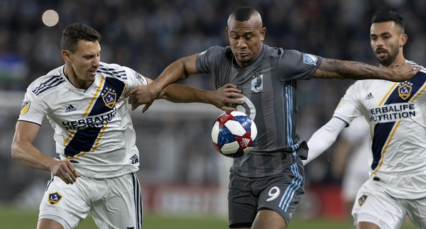 Angelo Rodriguez (9) of Minnesota United FC fought for the ball with Daniel Steres, left, of L.A. Galaxy in the Loons' first home playoff game on Oc