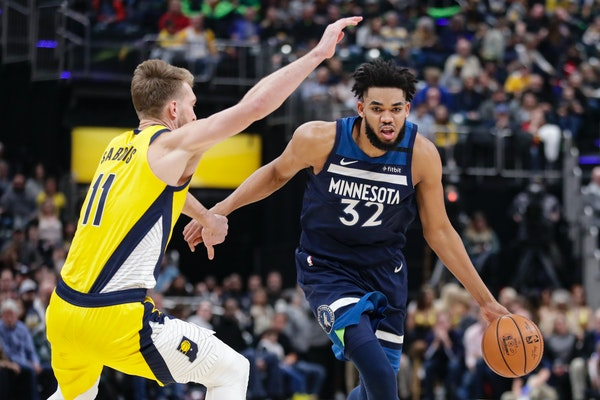 Timberwolves center Karl-Anthony Towns drives around Pacers forward Domantas Sabonis
