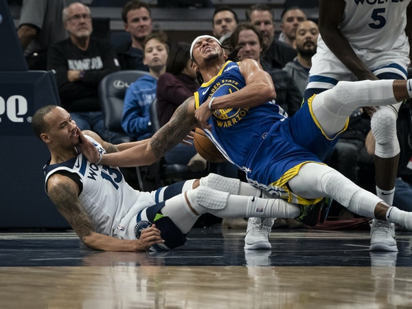 Wolves guard Shabazz Napier and Warriors guard Damion Lee tumbled to the ground after a first-half collision Thursday night at Target Center.