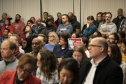 People stood in the back of the room when an overflow crowd attended the Minneapolis school board meeting in Minneapolis on Tuesday. Many parents atte
