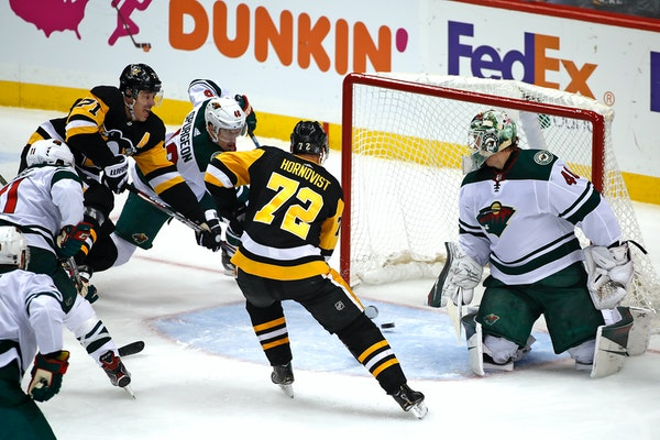 Pittsburgh's Evgeni Malkin (71) puts the puck behind Wild goaltender Devan Dubnyk with Jared Spurgeon defending for a goal during the first period