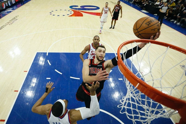 Chicago Bulls' Zach LaVine, center, goes up to shoot between Philadelphia 76ers' Tobias Harris