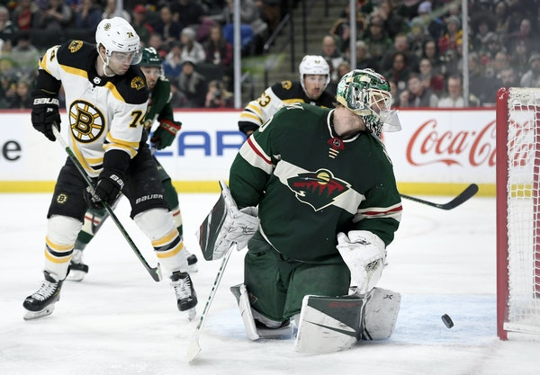 Wild goaltender Devan Dubnyk and Bruins left wing Jake DeBrusk watched as a shot by Torey Krug, not pictured, went into the net during the second peri