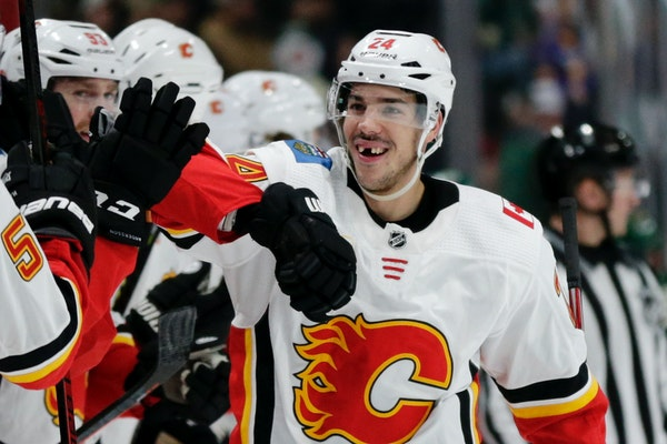 Calgary defenseman Travis Hamonic is congratulated by the bench after scoring a goal against the Wild in the first period