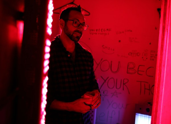 Biohacker Thaddeus Owen in a closet in the family's home where he bathes himself in red light each day before dawn.