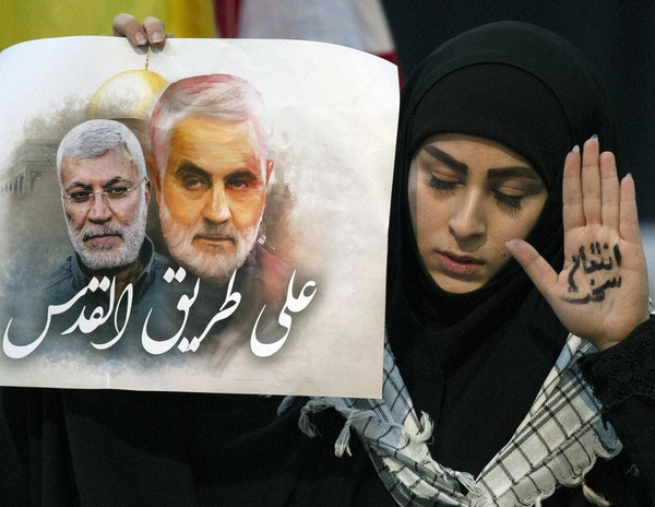 """A supporter of Hezbollah leader Sayyed Hassan Nasrallah wears the words """"powerful revenge"""" on her hand, ahead of the leader's televised speech in a so"""