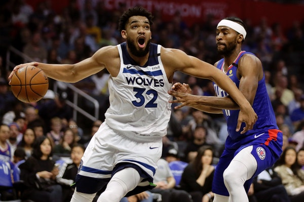 Minnesota Timberwolves center Karl-Anthony Towns, left, drives past Los Angeles Clippers forward Maurice Harkless during the first half of an NBA bask