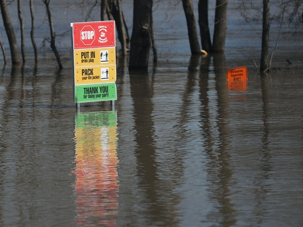 Signs were nearly underwater near Hwy. 19, where the Minnesota River caused flooding and closed down three of four highways heading into town last Mar