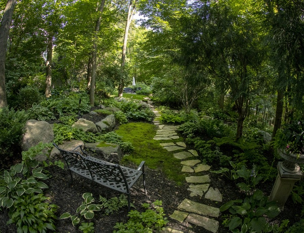 """Winding paths of limestone pavers link a series of mostly shaded garden """"rooms"""" in the woodland habitat at the Chanhassen home of Cindy and Mike C"""