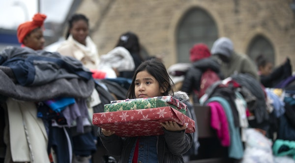Briella Jones 5, who lived in the Francis Drake Hotel apartments with her family, holds donated Christmas presents on Wednesday, Dec. 25, 2019, in Min