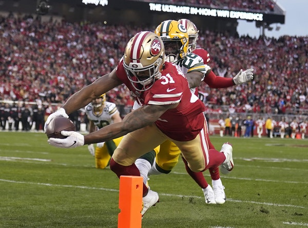San Francisco running back Raheem Mostert scores in front of Green Bay free safety Darnell Savage during the first half of the NFC Championship Game
