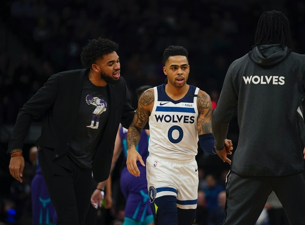 Timberwolves center Karl-Anthony Towns (left, encouraging new Timberwolves guard D'Angelo Russell in a recent game against Charlotte) is still out bec