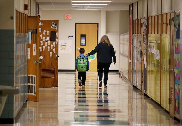 Jolie Holland, left, a nurse in the Howard Lake-Waverly-Winstead School district, comforted a student in 2019. Minnesota health officials said Sunday