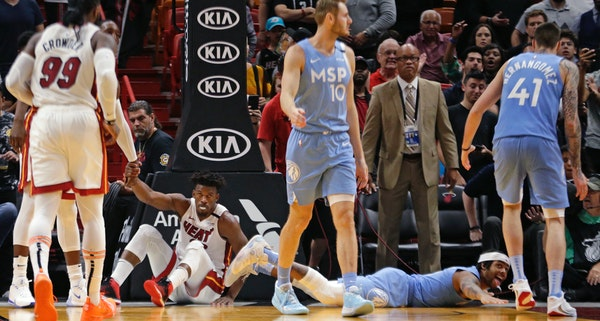 The Timberwolves' D'Angelo Russell, bottom right, reacts as the Heat's Jimmy Butler shows frustration after they both went down in the fourth quarter
