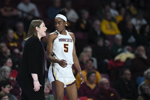 Gophers coach Lindsay Whalen talks things over with forward Taiye Bello in the second half against Iowa