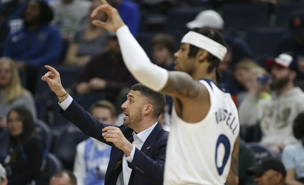 Timberwolves' head coach Ryan Saunders signals to his team alongside ' D'Angelo Russell during a game against the Dallas Mavericks.