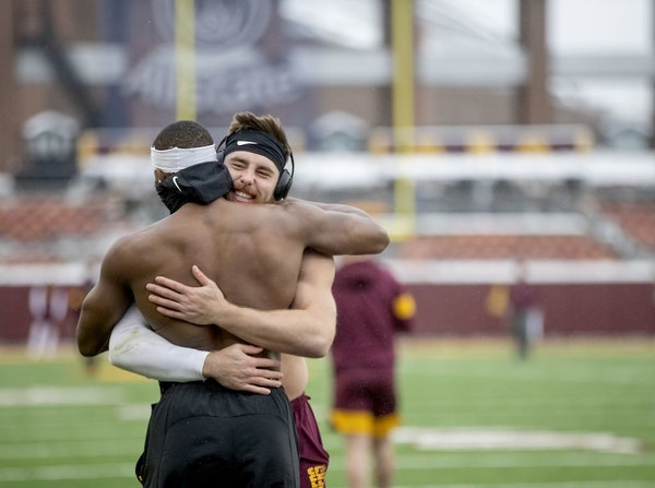 Gophers linebackers Carter Coughlin, right, and Kamal Martin, braved the cold and shared a hug while they were warming up before the Wisconsin game la