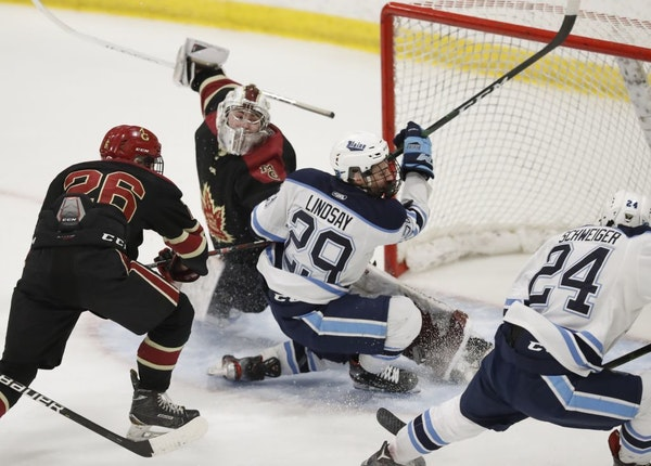 Blaine's Braeden Lindsay (29) attempts to get the puck in Maple Grove goal .