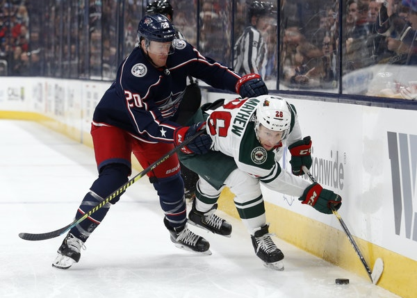 Columbus Blue Jackets forward Riley Nash, left, checks Minnesota Wild forward Gerald Mayhew during the first period of an NHL hockey game in Columbus,
