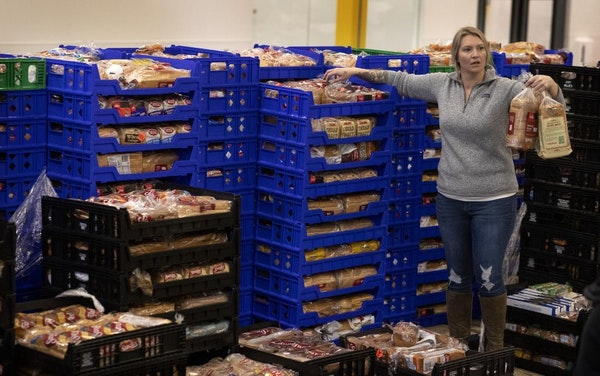 Megan Struxness of Minneapolis a volunteer , gathers loaves of bread at Second Harvest . Staff and volunteers at Second Harvest Heartland, the state's
