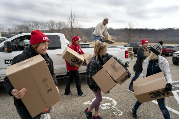 Registered nurse Kim Lutes left, and others carried 1,200 N95 masks donated by Rich Forstner, president of White Bear Lake contracting firm Mavo Syste