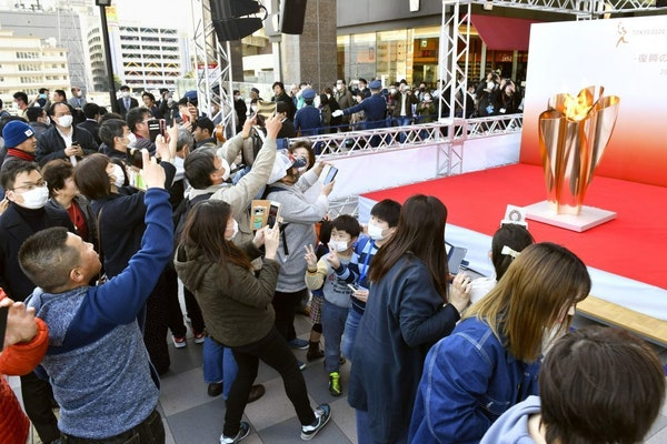People gathered to take a look at Olympic flame on display north of Tokyo as calls grew for the games to be postponed.