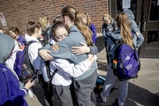 Members of the Rochester Lourdes girls' basketball team including, Marissa Houfek, left, and Ella Hopkins, hugged each other after they left Williams