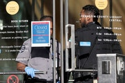 Security guards stand at the door to the downtown Minneapolis Public Library, turning away patrons after the library closed amid the coronavirus sprea