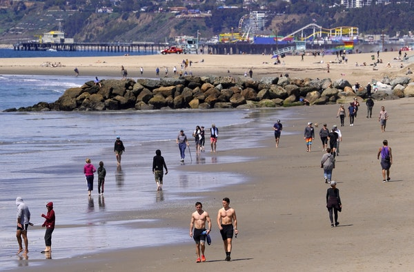 Beachgoers are seen at Venice Beach, Saturday, March 21, 2020, in Los Angeles. Traffic would normally be bumper-to-bumper during this time of day on a