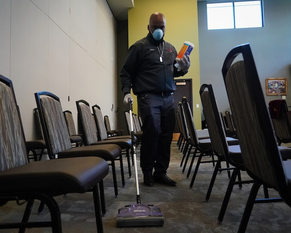 Bruce DeArmon, of Estes Funeral Chapel in Minneapolis, vacuumed and disinfected a chapel between memorial services.