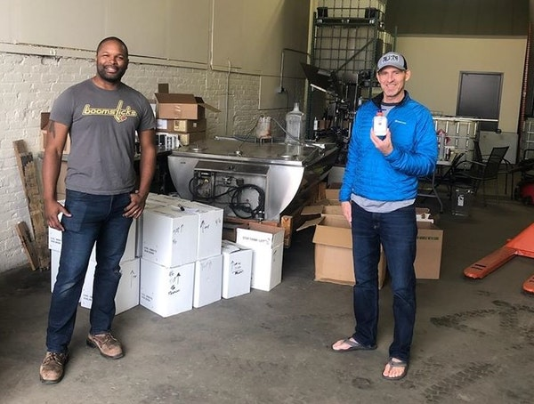Du Nord Craft Spirits owner Chris Montana (left) donates hand sanitizer to Lonny Evans (right) of Loaves & Fishes, the state's largest free meal pro