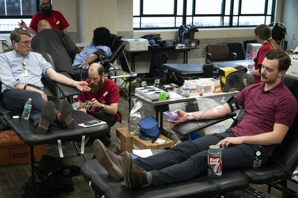 Ben Pelton, right, and Dr. Timothy Sielaff, who was assisted by Travis Wolfe of the Red Cross, donated blood at Allina Commons on March 19. State heal