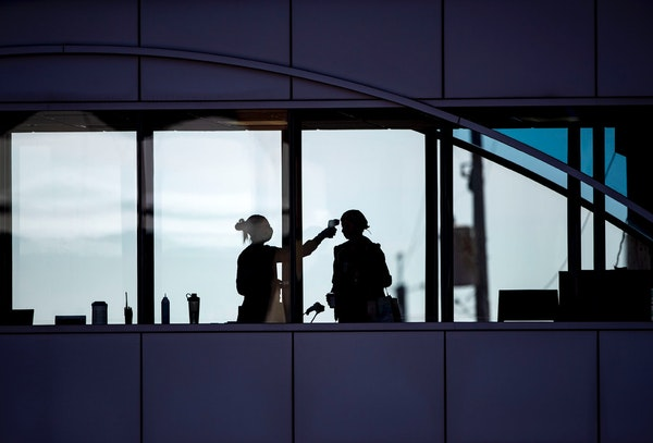 A health care worker takes the temperature of a visitor to Essentia Health who was crossing over a skywalk bridge from the adjoining parking deck in D