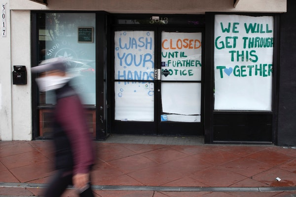 A man passes a store that closed as part of efforts to combat the spread of the new coronavirus. About one in 10 U.S. workers lost jobs in the past th