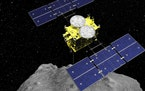 In this computer graphics image released by the Japan Aerospace Exploration Agency (JAXA), the Hayabusa2 spacecraft is seen above on the asteroid Ryug