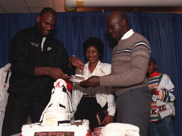 Michael Jordan serves his father, James, right, a slice of birthday cake while his mother, Deloris watches during a party in honor of Jordan's 26th bi
