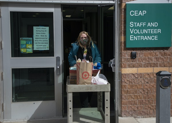 Natasha Triplett pushed a cart of food to a car Wednesday morning at the CEAP office in Brooklyn Center. The nonprofit is seeing a 25% increase in the