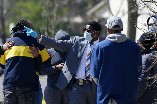 Sgt. Christopher Gaiters, center, talked with bystanders at the scene of a homicide Saturday in the 1100 block of Irving Avenue N. in Minneapolis.