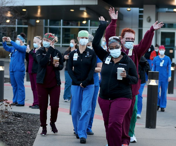 Regions Hospital healthcare workers came outside the hospital Wednesday to thank Xcel Energy crew members who had gathered outside Regions Hospital to
