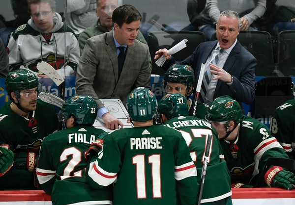 Wild interim head coach Dean Evason, right, speaks to his players along with assistant coach Darby Hendrickson on March 1.