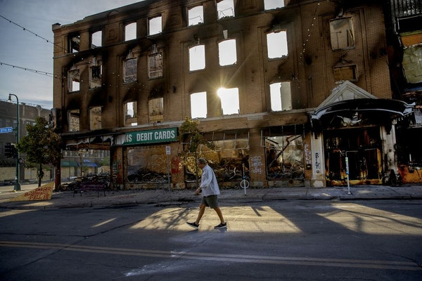 A man walked in front of a burned-out building Sunday morning on S. 27th Avenue at Lake Street, May 31, 2020, in Minneapolis.