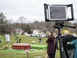 Guests mourn during a live-streamed funeral in March. The pandemic has made in-person funerals difficult to hold and many families are struggling with