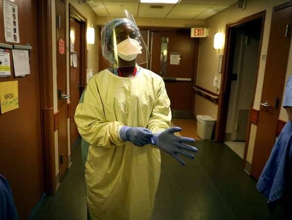 Registered nurse Syndie Pascal dons personal protective equipment before checking a COVID-19 patient on the fifth floor ICU at Bethesda Hospital in St