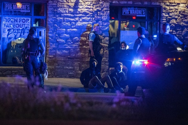 People in a vehicle are detained on Washington Avenue by Minneapolis Police in downtown Minneapolis after curfew.