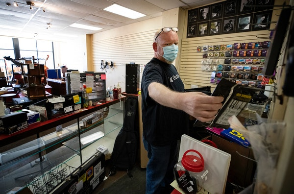 Ted Vig arranged bass strings on the wall at Vig's guitars in St. Paul. Looters trashed the tiny shop and stole instruments and equipment valued at $4