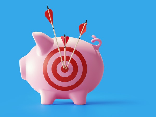 Piggy bank with bulls eye target and red arrows standing on blue background. Horizontal composition with copy space. Great use for financial concepts.